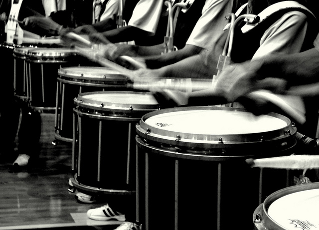 Image focused on drumsticks beating in a marching band drumline