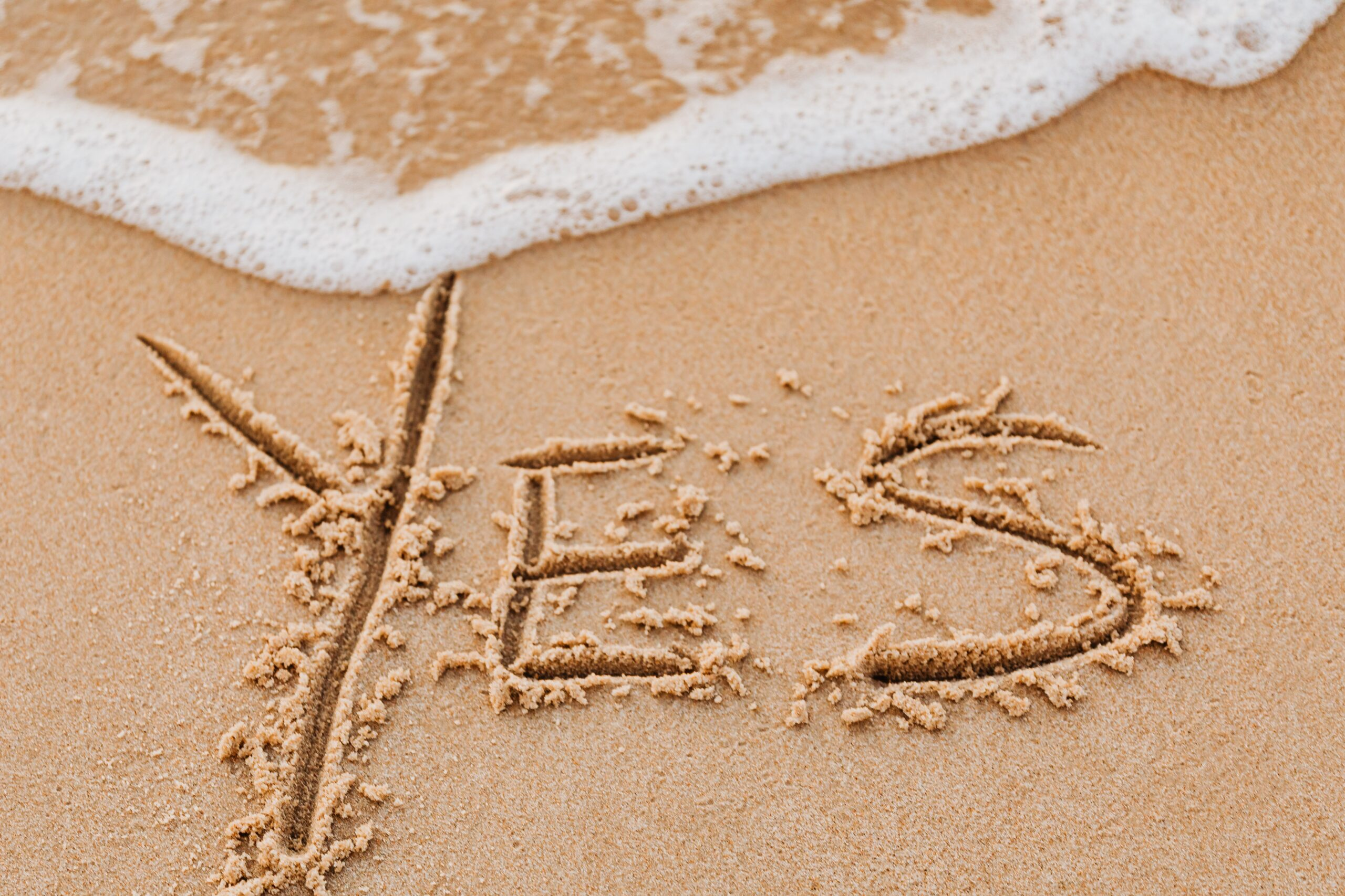 The word YES carved in sand.