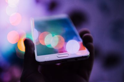 photo of mobile phone in hand, reflecting colors